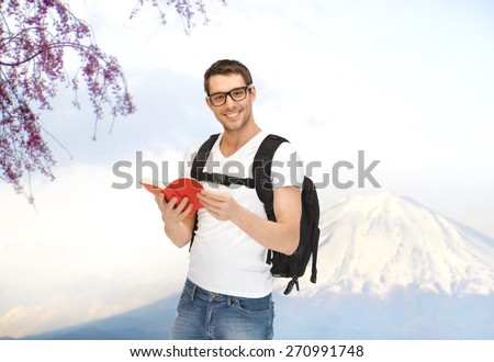 people, travel, tourism, japan and education concept - happy young man in eyeglasses with backpack and book travelling over fuji mountain background - stock photo