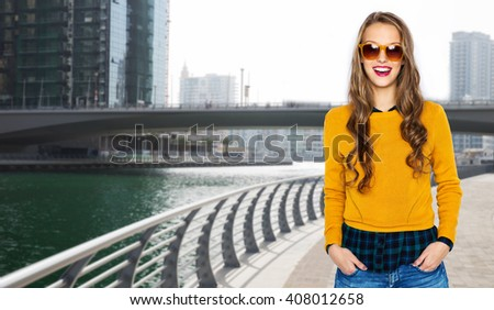 people, travel, tourism, style and fashion concept - happy young woman or teen girl in casual clothes and sunglasses over dubai city street background - stock photo