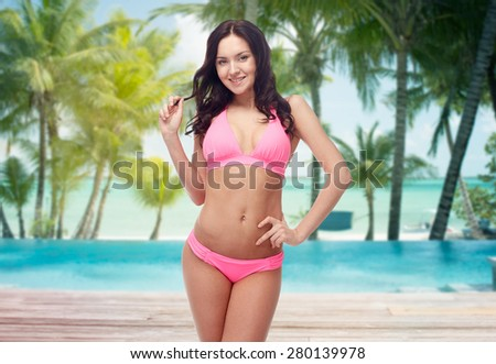 people, travel, tourism, summer and sexual concept - happy young woman posing in pink bikini swimsuit over swimming pool and beach with palm trees background - stock photo