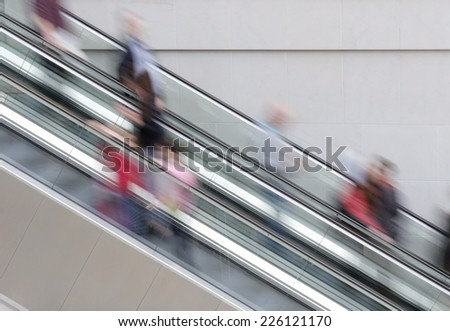 People traveling on escalator taking with slow shutter speed to show movement - stock photo