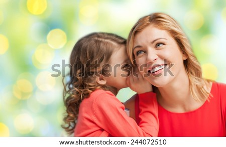 people, trust, love, family and motherhood concept - happy daughter whispering gossip to her mother over green lights background - stock photo