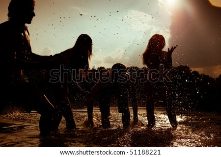 People (two couples) feeling very free in the sunset standing in the water splashing water at each other having an unbelievable amount of fun. Silhouettes. - stock photo