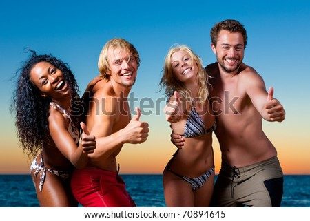 People (two couples) on the beach having a party and having a lot of fun in the sunset