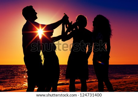 People (two couples) on the beach having a party, drinking and having a lot of fun in the sunset (only silhouette to be seen, people having bottles in their hands with the sun shining through) - stock photo