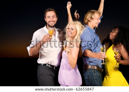 People (two couples) on the beach having a party, drinking and having a lot of fun in the sunset, they are wearing smart casual clothes and drink champagne