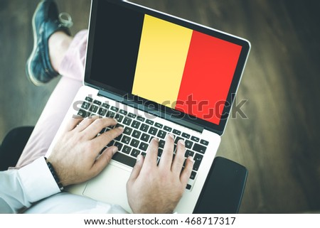 People using laptop and showing on the screen the flag of BELGIUM