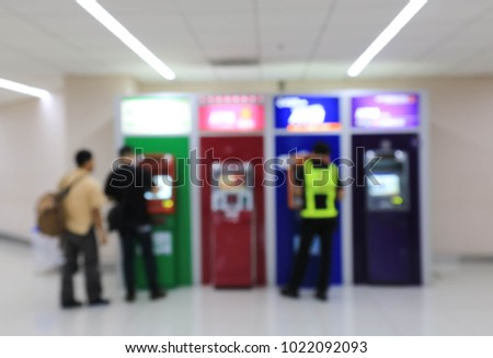 People using the bank machine to transfer and withdraw their money