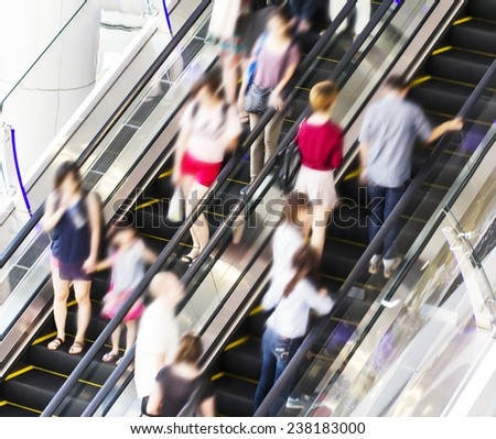 People using the escalator. Motion blur. - stock photo