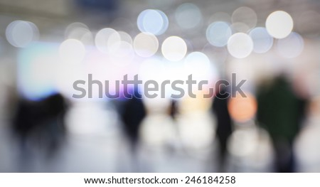 People visit a trade show, generic background, humans and location not recognizable. Intentionally blurred post production. - stock photo