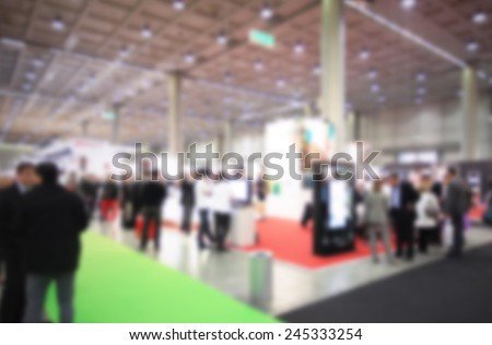 People visit a trade show, humans not recognizable. Intentional blurred post production. - stock photo