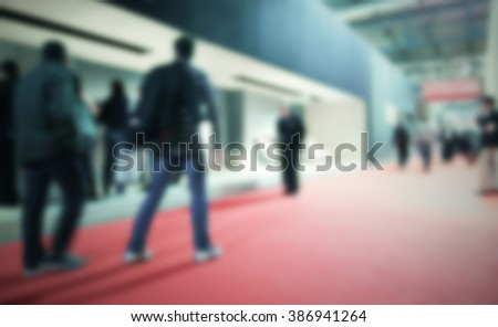 People visit an interiors design exhibition. Background with an intentional blur effect applied.