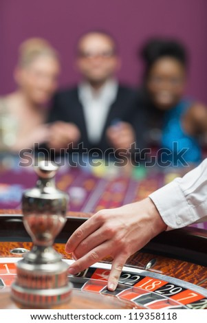 People waiting for roulette wheel in casino - stock photo