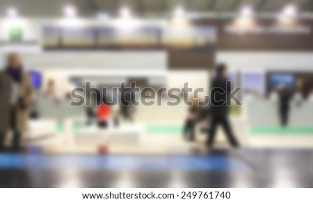 People walk at trade show exhibition. Intentionally blurred editing post production background. - stock photo