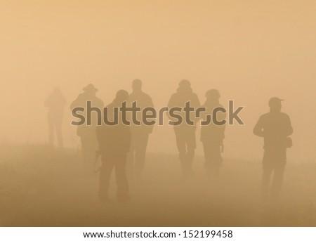 People walk on foggy morning - stock photo
