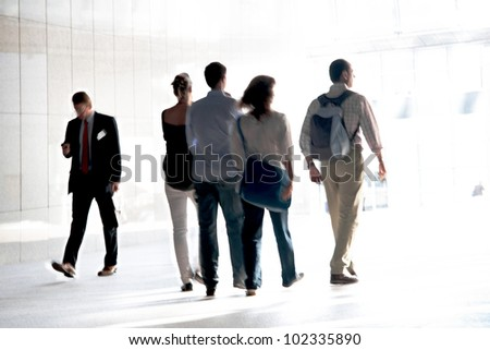 People walking against a light background. Walking businessmen against a background of an urban landscape. - stock photo