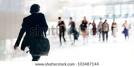 People walking against the light background of an urban landscape. Motion blur. - stock photo
