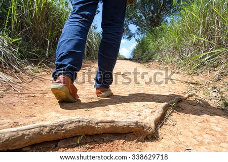 People walking alone on walkway,Hiking alone on a dirt walkway