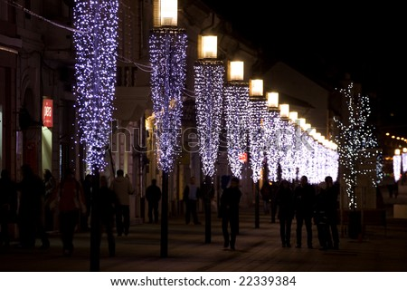 People walking along a row of lights - stock photo