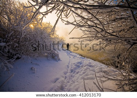 People walking along the shore of a unfrozen river near trees covered snow. Frame of branches. beautiful winter landscape - stock photo