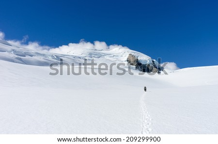 People walking among snows of New Zealand mountains - stock photo