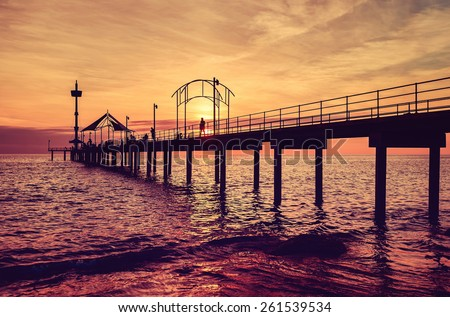 People walking and fishing on jetty at sunset - stock photo