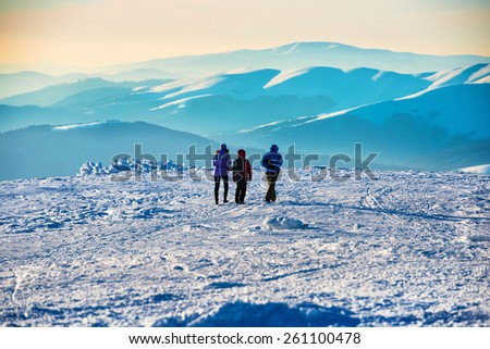 People walking at sunset in winter mountains covered with snow