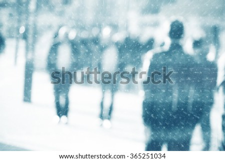 People walking down the street in the evening, beautiful light at sunset. The photo is purposely made out of focus, no faces are recognisible - stock photo