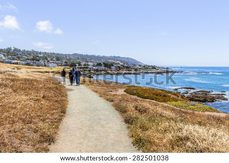 People walking, hiking, running, on a trail, boardwalk, next to the Big Sur coast on the California Central Coast, near Cambria, CA. - stock photo