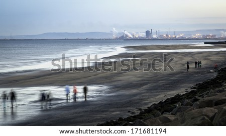 People walking in a cold day on Hartlepool beach North East of England - stock photo