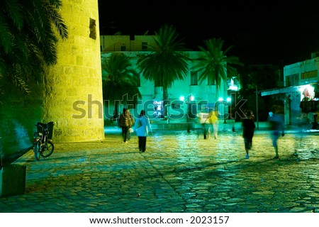 People walking in arabian medina by night - stock photo