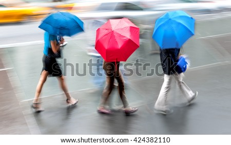 people walking in the street on a rainy day motion blurred - stock photo