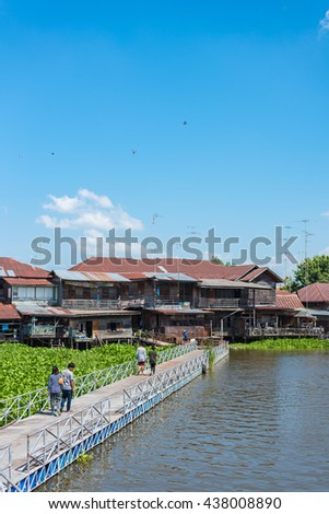 People walking into the Sriprachan Old Market, in Suphanburi province, Thailand. Selective Focus. - stock photo