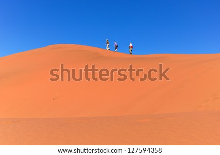 People walking on beautiful dune of Namib desert, traveling and hiking in South Africa