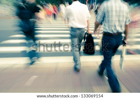 people walking on big city street, blurred motion zebra crossing abstract - stock photo
