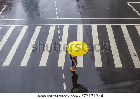 People walking on big city street, blurred motion zebra crossing abstract in the rain. - stock photo