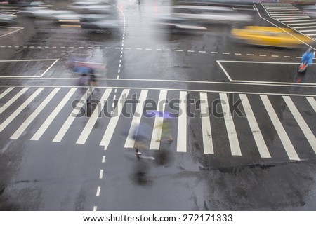 People walking on big city street, blurred motion zebra crossing abstract in the rain.