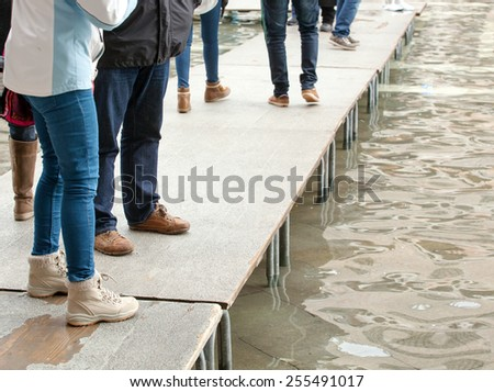 People walking on catwalk in Venice during the high tide.