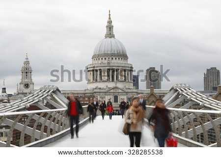 People walking on millennium bridge, St Paul's Cathedral, locates at the top of Ludgate Hill in the City of London, in the back ground
