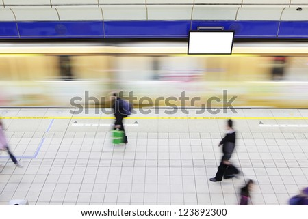 people walking on platform at a metro railway station with motion blur speed train and blank tv billboard, shot in Taipei, Taiwan, asia - stock photo