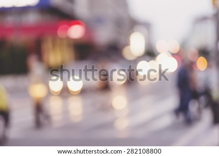 people walking on street in urban city, defocused image, city scene - stock photo