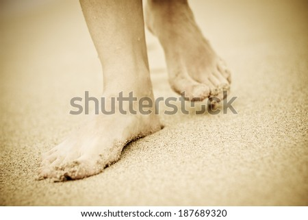 People walking on the beach leaving footprints in the sand. Horizontal image with dark vignette effect. Sri Lanka, Ceylon - stock photo