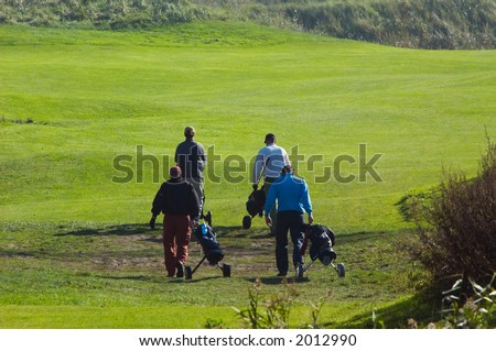 people walking on the golf course - stock photo