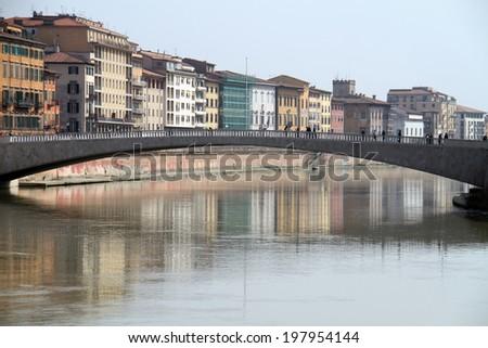 People walking over a bridge across Arno river in Pisa, Italy - stock photo