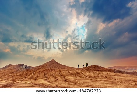 People walks on hills of active mud volcanoes in Buzau, Romania at sunrise. Dramatic sky colors and textured land.