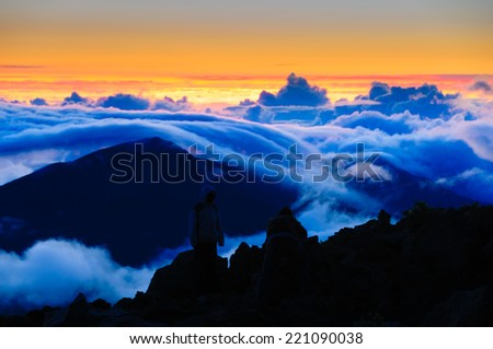 People watching clouds at sunrise from the top of Haleakala Crater on Maui, Hawaii, USA - stock photo
