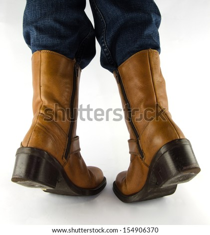 People wearing blue jeans, brown leather western cowboy boots standing on white background.