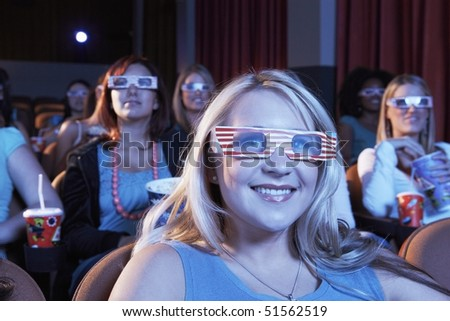 People wearing 3-d glasses watching 3-D movie in theatre - stock photo