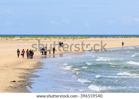 People who walk on the beach - stock photo