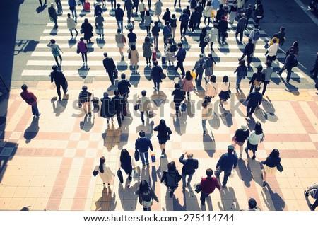 People who walk the crosswalk to dusk - stock photo