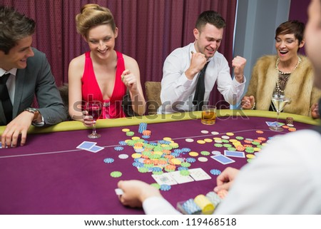 People winning in poker game in casino - stock photo